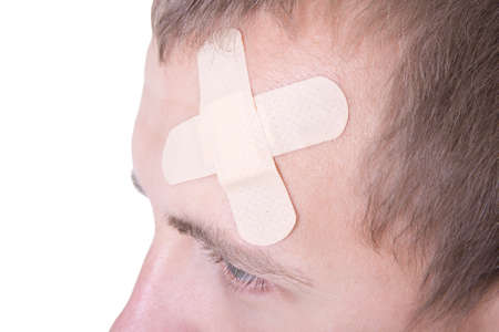close up of adhesive medical plaster on male forehead