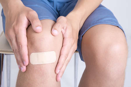 human knee: young man with adhesive bandage on his knee Stock Photo