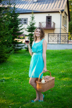 picnic park: happy woman with picnic basket drinking wine in summer park