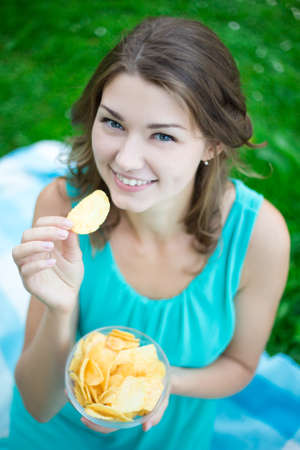 potato chips: close up portrait of cute young woman eating potato chips