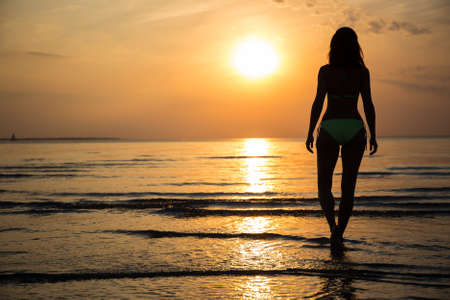 silhouette of young slim woman in bikini walking on beach at sunset
