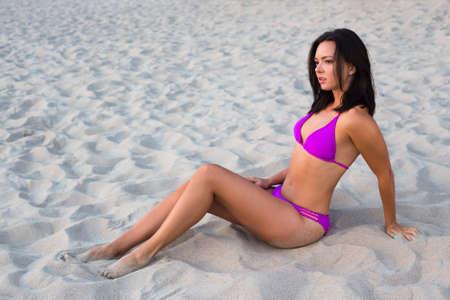 hot bikini: beautiful slim sporty woman in bikini sitting on sandy beach