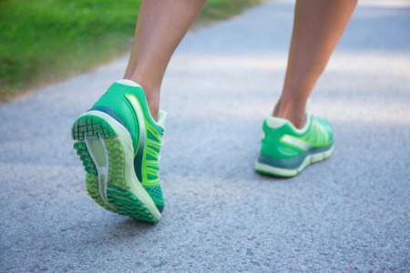 the sole of the shoe: close up of jogging woman in green running shoes Stock Photo