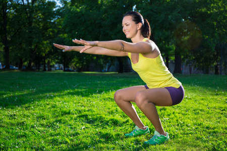 squat: beautiful woman working out in summer park