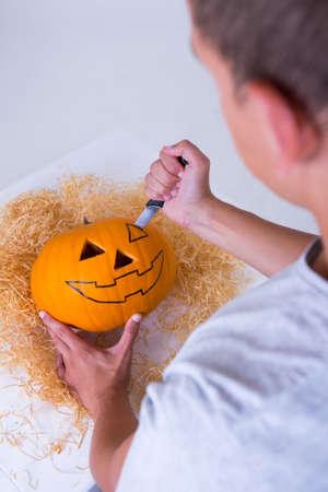 jack'o'lantern: man carving big pumpkin Jack-O-Lantern for Halloween Stock Photo