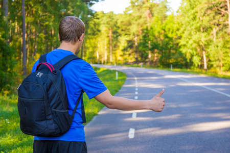 tourists stop: back view of young man hitchhiking on forest road