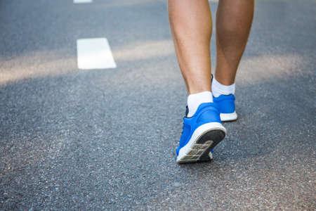 piernas: piernas masculinas en zapatos para correr fuera de la carretera de asfalto