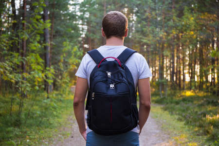 mochila viaje: rear view of man with backpack hiking in forest