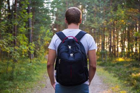 mochila viaje: Vista posterior del hombre con mochila senderismo en el bosque Foto de archivo