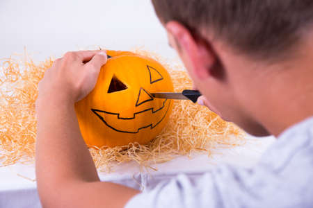 young knife: young man with knife preparing pumpkin for Halloween