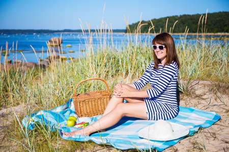 one girl: beautiful woman with picnic basket sitting on the beach Stock Photo