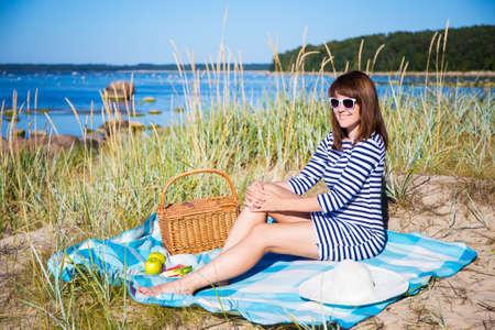 sunglasses beach: beautiful woman with picnic basket sitting on the beach Stock Photo