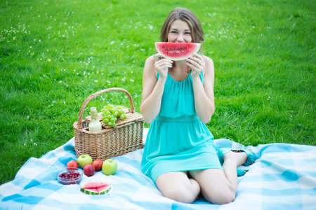 melons: woman with picnic basket holding slice of watermelon in summer park Stock Photo