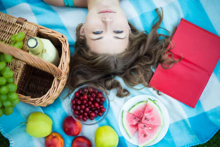 fruit: top view of beautiful woman with picnic basket, fruits and book in summer park Stock Photo