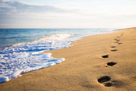 close up van voetafdrukken op het strand met gouden zand Stockfoto