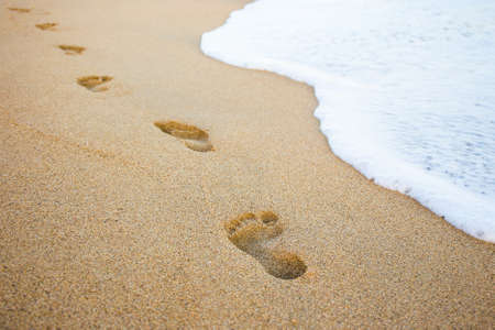 close up of footprints in the sand and sea wave Фото со стока