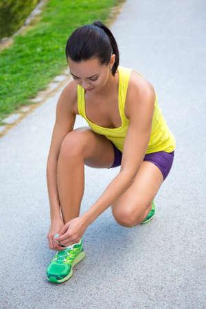 shoe laces: sporty slim woman tying shoe laces in park
