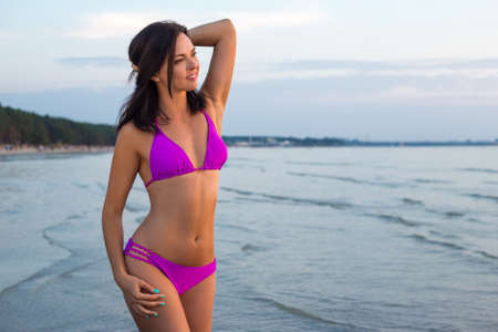 young beautiful slim woman in bikini posing over sea background