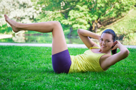 abdominal muscles: sporty woman doing exercises for abdominal muscles in summer park Stock Photo