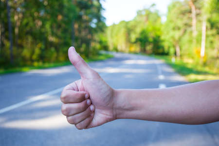 hitch hiker: close up of male hand hitching car on road Stock Photo