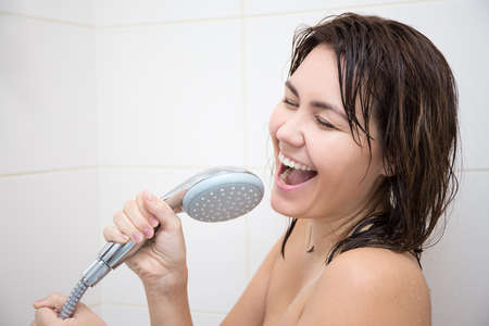 shower head: portrait of happy funny woman singing in shower Stock Photo