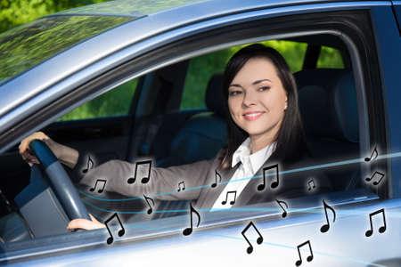 personas escuchando: Mujer de negocios feliz escuchando música en el coche Foto de archivo