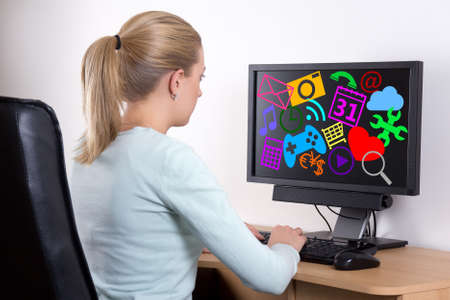 personal computer: back view of woman with personal computer using media applications in office Stock Photo