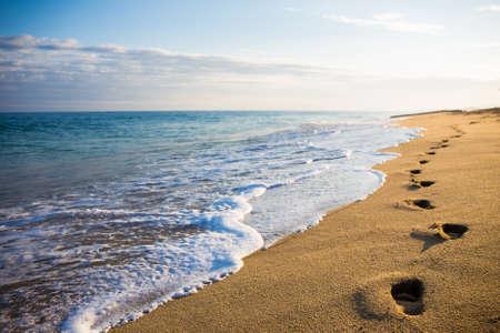 huellas pies: de cerca de huellas en la arena en la playa al atardecer