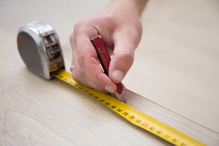 men working: close up of male hands with measuring tape and new laminated wooden floor