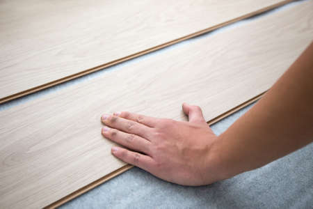 lying on floor: close up of male hands installing new laminated wooden floor