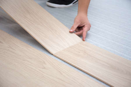 laminated: male hands installing new laminated wooden floor Stock Photo