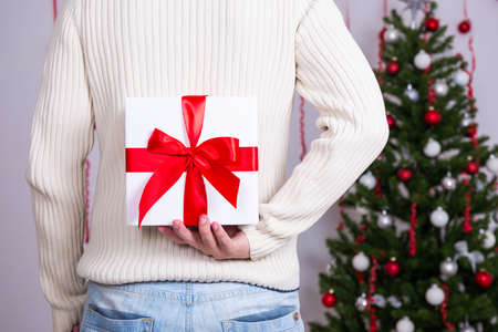 gift behind back: Christmas surprise concept - man hiding gift box behind back