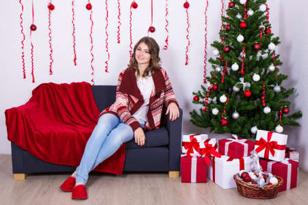 ropa casual: young beautiful woman sitting in decorated living room with Christmas tree