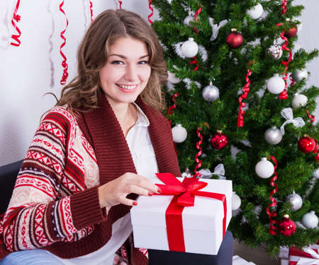 opening gift: happy young beautiful woman opening gift box near christmas tree Stock Photo