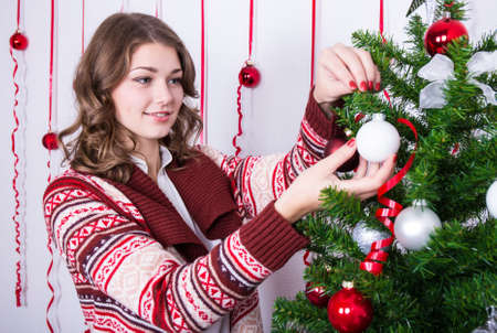 decorating christmas tree: portrait of happy young woman decorating Christmas tree