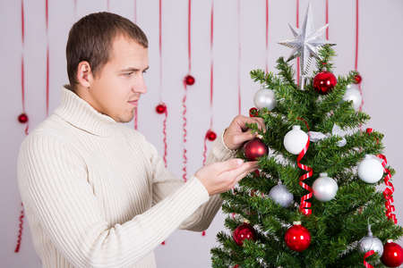 decorating christmas tree: portrait of young handsome man decorating Christmas tree Stock Photo