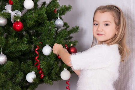 home decorating: beautiful little girl decorating Christmas tree at home