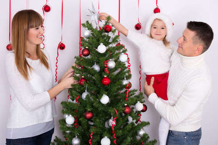 home decorating: young happy family decorating Christmas tree at home Stock Photo