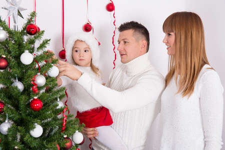 decorating christmas tree: happy parents and little daughter decorating Christmas tree