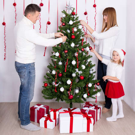 home decorating: young happy parents and daughter decorating Christmas tree at home