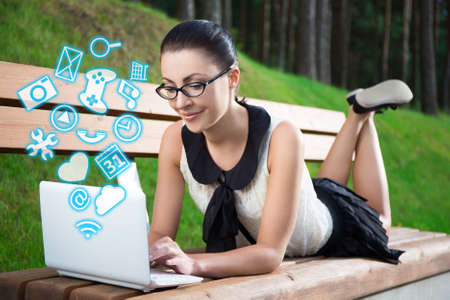 girl with laptop: girl in school uniform using laptop with different applications lying on bench in summer park