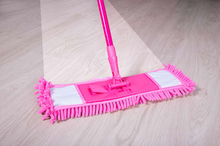 bright housekeeping: close up of wooden floor with pink mop - before and after concept