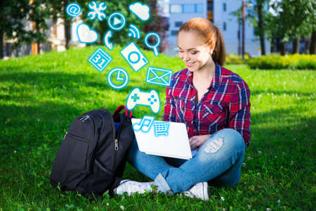 laptop outside: teenage student or school girl using laptop with different applications in summer park