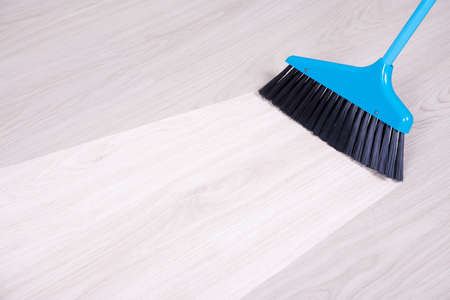 bright housekeeping: before and aftet cleaning concept - blue broom sweeping parquet floor Stock Photo