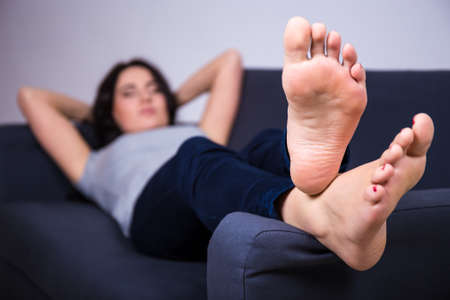 lying on couch: relaxation concept - close up of female legs lying on sofa at home Stock Photo