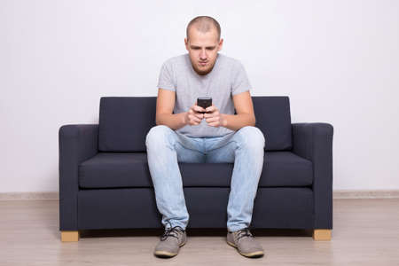 handsome man sitting on sofa with mobile phone at home 版權商用圖片
