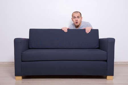 asustado: joven escondido detrás de un sofá en casa