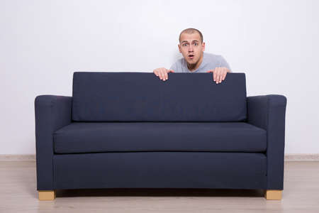 young fear: young man hiding behind a sofa at home