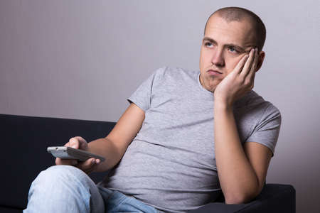 young bored man sitting on sofa and watching movie or tv