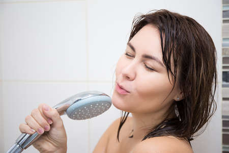 portrait of young happy woman singing in shower Stock Photo